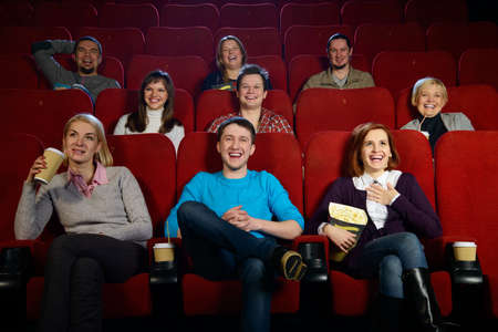 Group of smiling people watching movie in cinema photo