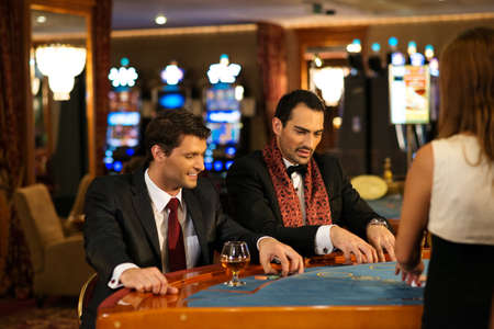 casino tokens: Two young cheerful men behind table in a casino