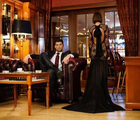 wealthy lifestyle: Elegant couple in formal dress in luxury cabinet