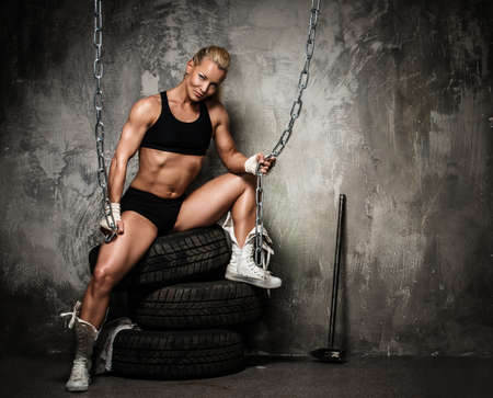 body pump: Beautiful muscular bodybuilder woman sitting on tyres and holding chains