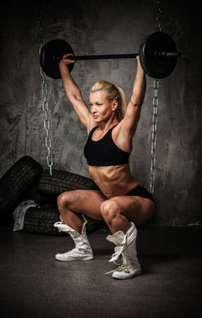 Beautiful muscular bodybuilder woman doing exercise with weights