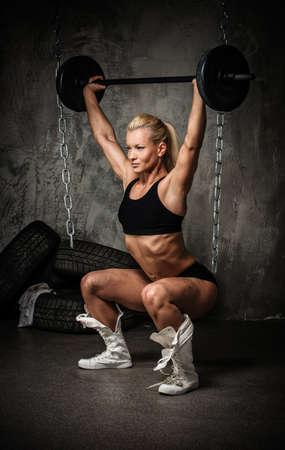 haciendo ejercicio: Hermosa mujer culturista musculoso haciendo ejercicio con pesas