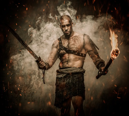 Gladiator standing in a smoke with torch and sword photo