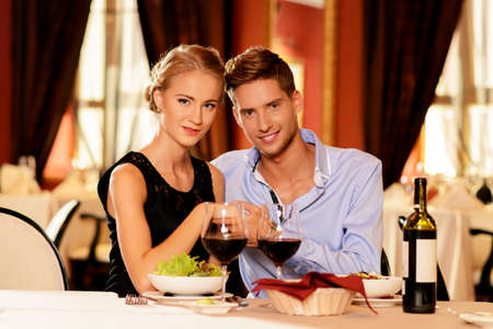 romantic dinner: Beautiful young couple with glasses of wine in restaurant Stock Photo