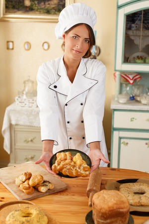 baked goods: Woman cook holding plate with homemade baked goods