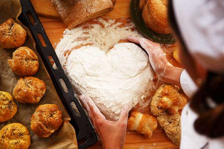 haciendo pan: Las manos del cocinero que prepara la pasta para los pasteles caseros