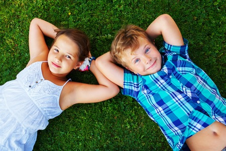 lying on grass: Happy children lying on a meadow