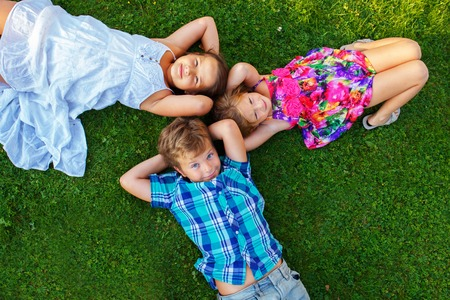 Happy children lying on a meadow photo
