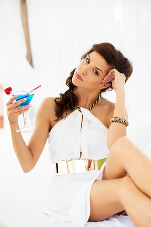 Beautiful brunette girl  in white dress with cocktail under summer awning  Stock Photo - 22783199