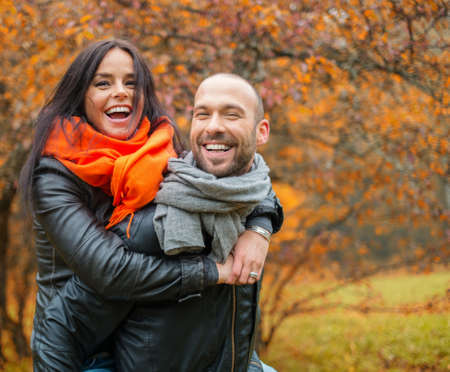 Happy middle-aged couple outdoors on beautiful autumn day photo