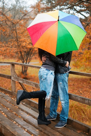 man woman hugging: Middle-aged couple with umbrella outdoors on beautiful rainy autumn day
