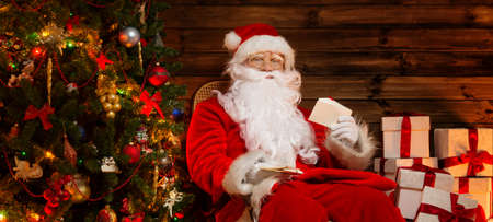 christmas costume: Santa Claus sitting on rocking chair in wooden home interior with letters in hands