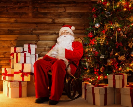 Santa Claus sitting on rocking chair in wooden home interior with gift boxes around him  photo