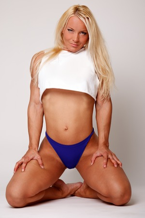 Sexy blond sporty woman in white top and blue panties  photo