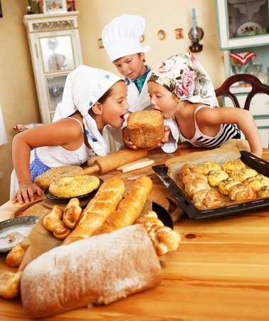 Happy children with table full of  homemade pastry photo