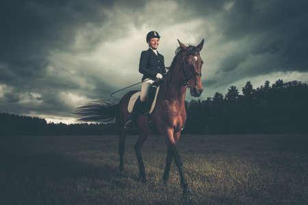 femme et cheval: Belle fille assise sur un cheval en plein air contre le ciel maussade