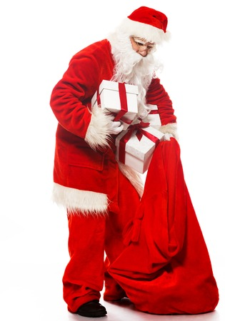Santa Claus with christmas sack and gift boxes isolated on white  Stock Photo