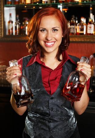Beautiful redhead barmaid with bottles behind bar counter  photo