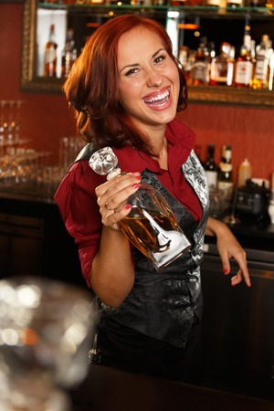 Beautiful redhead barmaid with bottle behind bar counter  photo