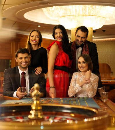 fichas de casino: Grupo de j?venes detr?s de la mesa de ruleta en un casino