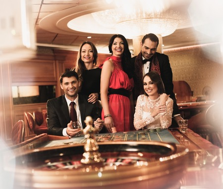 Group of young people behind roulette table in a casino photo
