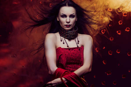 Beautiful vampire woman in red dress with waving hair photo
