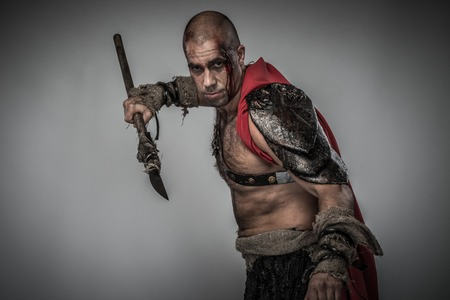 spears: Wounded gladiator in red coat with spear