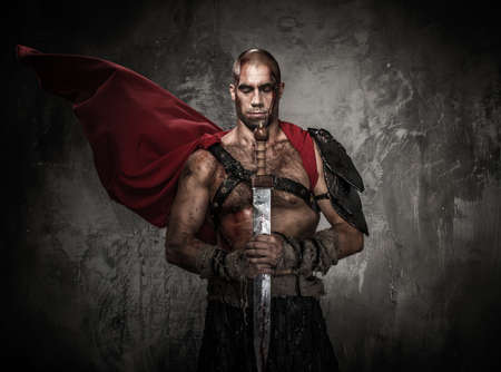 Wounded gladiator holding sword covered in blood with both hands photo