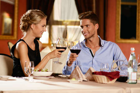 Drinking wine: Beautiful young couple with glasses of wine in restaurant Stock Photo