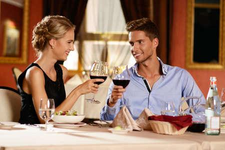 bebiendo vino: Pareja joven hermosa con los vidrios de vino en el restaurante