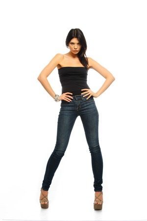 Young beautiful brunette woman in black top and jeans isolated on white  photo
