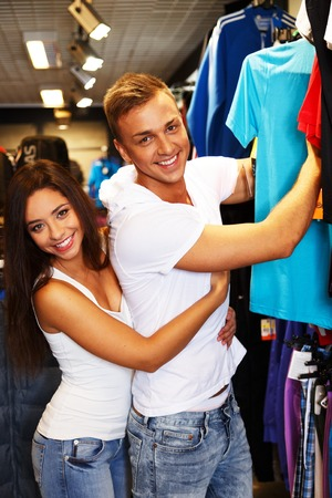 Beautiful young couple choosing sportswear in sport outlet photo