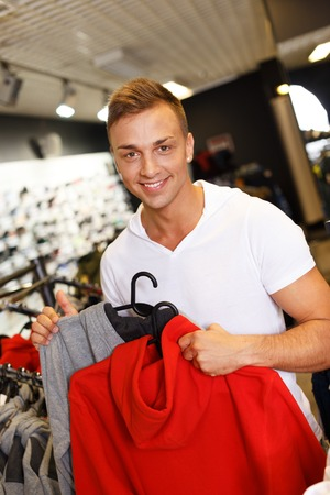 Handsome young man choosing sports wear in a sport outlet photo