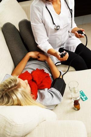 Female doctor measuring sick girls blood pressure  photo