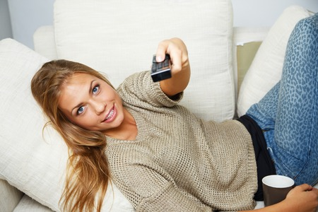 Young beautiful woman on a sofa with remote control and mug photo