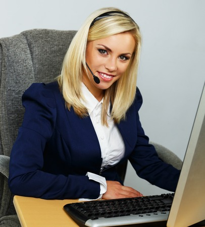 Beautiful blond help desk office support woman with headset photo