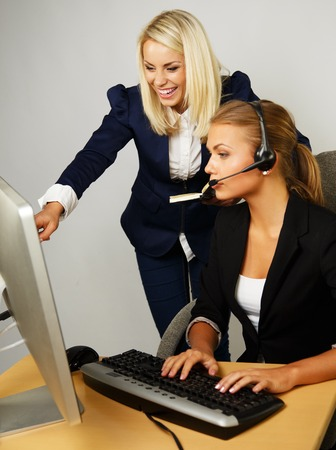 Beautiful help desk office support woman with female boss behind her photo