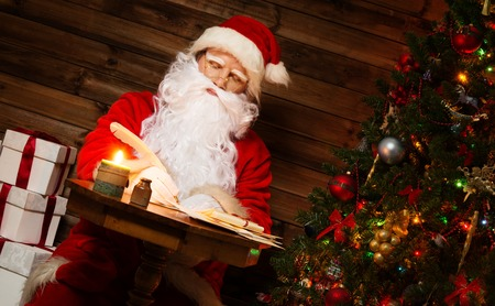 Santa Claus in wooden home interior sitting behind table and writing letters with quill pen photo
