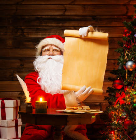 christmas costume: Santa Claus in wooden home interior holding blank wish list scroll