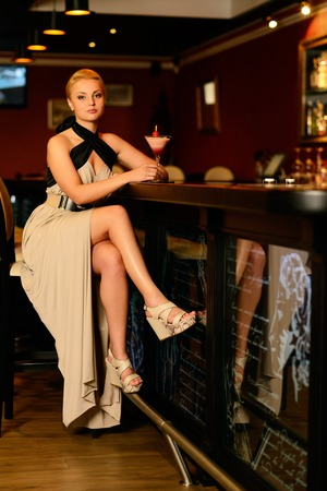 Beautiful blond woman in evening dress sitting near bar counter with cocktail photo