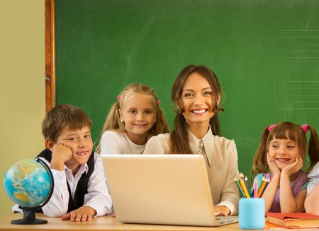 Group of happy classmates with their teacher in class near blackboard  photo