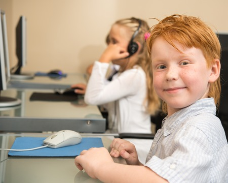 Little redhead schoolboy in front of desktop computer in school  photo