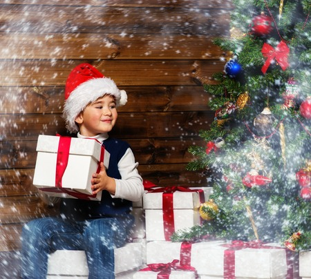 ard: LIttle boy in Santa hat with gift box under christmas tree in wooden house interior