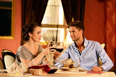Beautiful young couple with glasses of wine in restaurant photo