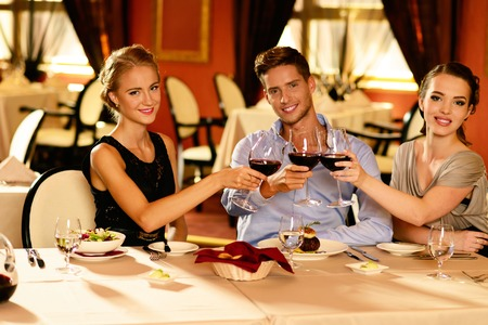 Young friends with glasses of red wine in a luxury restaurant  photo