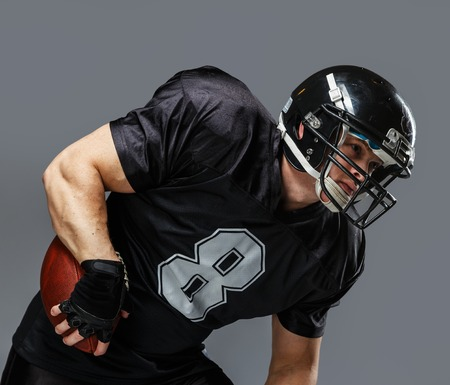 American football player with ball wearing helmet and jersey  photo