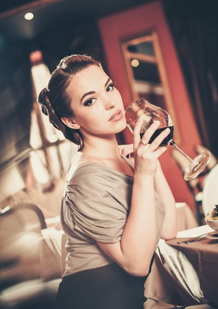 copa de vino: Hermosa joven con un vaso de vino tinto solos en un restaurante