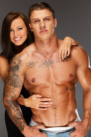 Young woman embracing man with muscular torso  photo