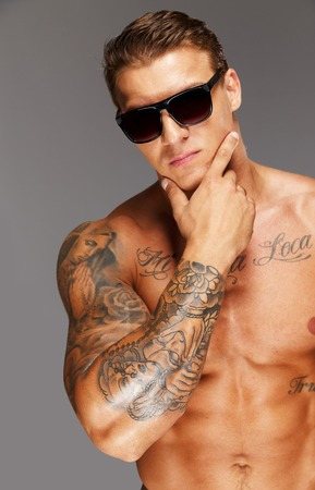 hot guy: Handsome man in sunglasses with muscular tattooed torso