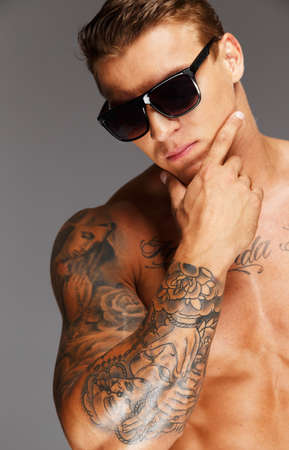 tattooed: Handsome man in sunglasses with muscular tattooed torso